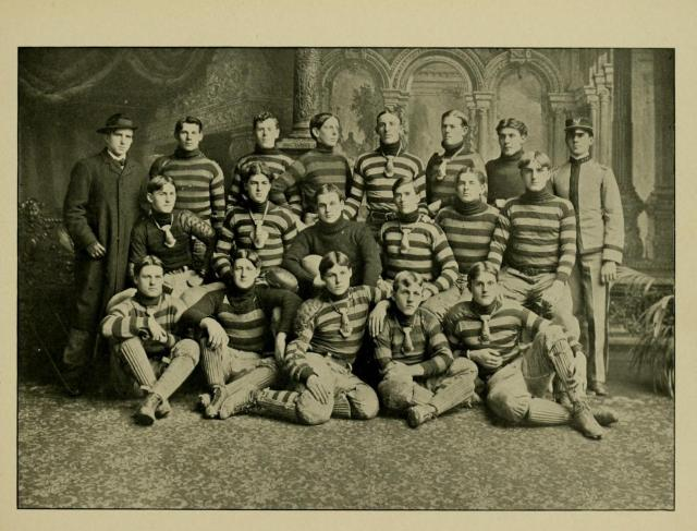 The 1903 M.A.C. football squad.  Coach Markey is at the far left in the black coat.